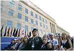 "Sitting in front of the rebuilt section of the Pentagon, service personnel and families listen to President George W. Bush at the Pentagon Observance Wednesday, Sept. 11, 2002. ""One year ago, men and women and children were killed here because they were Americans. And because this place is a symbol to the world of our country's might and resolve,"" said the President. ""Today, we remember each life. We rededicate this proud symbol and we renew our commitment to win the war that began here."""
