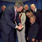 March of Dimes Ambassador Justin Lamar Washington donates one dollar to President Bush as his contribution to assist Afghan children.