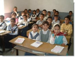 Iraqi primary school children enjoy a new day of education in their newly rehabilitated class room.