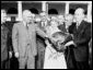 Photograph of President Truman receiving a Thanksgiving turkey from members of the Poultry and Egg National Board and other representatives of the turkey industry, outside the White House.