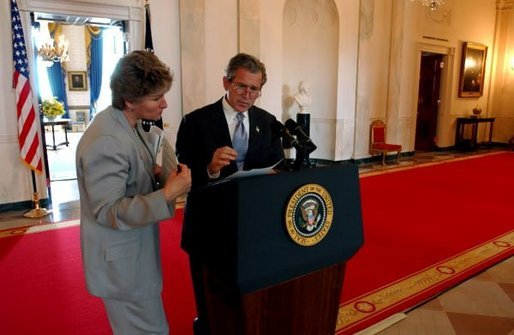 President George W. Bush discusses a speech with Karen Hughes in the Cross Hall of the White House June 6, 2002. White House photo by Eric Draper.