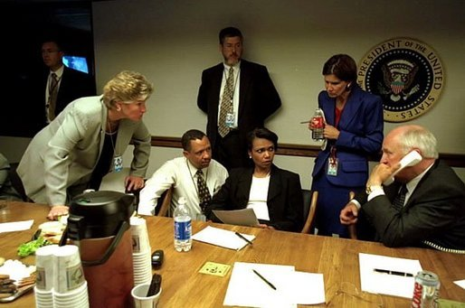 As Vice President Dick Cheney talks on the phone, Karen Hughes listens with fellow White House staff members in the Presidential Emergency Operations Center Sept. 11, 2001. White House photo by David Bohrer.