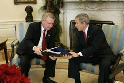 President George W. Bush receives the results of the 2004 Monitoring the Future study from Director John Walters of the Office of National Drug Control Policy in the Oval Office Tuesday, Dec. 21, 2004. The study measures drug, alcohol and cigarette use among adolescent students nationwide. This year's report found that drug use among teens has declined 17 percent since 2001.
