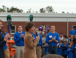 White House Fellows volunteer time in Louisiana to build a playground at a school devastated by Hurricane Katrina. First Lady Laura Bush speaks at the ribbon-cutting ceremony.