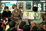 "Mrs. Bush and an interpreter listen as Princess Hisako Takamado reads a book she has written, ""Katie and the Dream-Eater"", to students at Akashi Elementary School, Monday, February, 18, 2001."