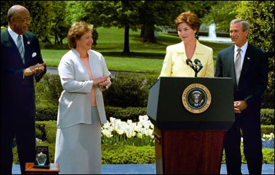 President George W. Bush and Laura Bush honor the 2003 National and State Teacher of the Year, Betsy Rogers, during a ceremony in the East Garden, April 20, 2003. Education Secretary Rod Paige stands to the left. White House photo by Tina Hager.