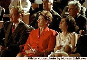 Georgetown University President John J. DeGioia, Laura Bush, and Theresa DeGioia, who is holding young J.T. DeGioia, listen to speakers at the White House Summit on Early Childhood Cognitive Development at Georgetown University, July 26-27, 2001. White House photo by Moreen Ishikawa.