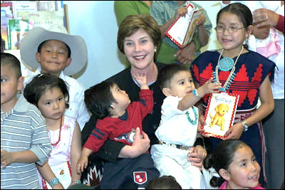 Children at the Kayenta Indian Health Service Clinic on the Navajo Nation gather around Mrs. Bush after reading with her May 8 , 2003.