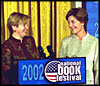 Laura Bush welcomes Ludmila Putina, wife of Vladimir Putin, President of the Russian Federation, to the Second Annual National Book Festival Saturday, October 12, 2002 in the East Room of the White House. Standing with the First Ladies on stage are, left to right, Native American poet Lucy Tapahoso, writer Mary Higgins Clark, Librarian of Congress James Billington, and NBA player Jerry Stackhouse.