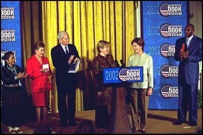 Laura Bush welcomes Ludmila Putina, wife of Vladimir Putin, President of the Russian Federation, to the Second Annual National Book Festival Saturday, October 12, 2002 in the East Room of the White House. Standing with the first ladies on stage are, left to right, Native American poet Lucy Tapahoso, writer Mary Higgins Clark, Librarian of Congress James Billington, and NBA player Jerry Stackhouse. White House photo by Susan Sterner.