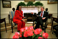 President George W. Bush and Coretta Scott King, the widow of Dr. Martin Luther King, Jr., share a laugh in the Oval Office Jan. 21, 2002. President George W. Bush honored Dr. King in a White House celebration and received a portrait of the civil rights leader from his wife and children in the East Room.
