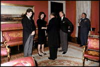 With her brother-in-law Edward Kennedy at her side, Jacqueline Kennedy greets guests in the Red Room following the funeral for her husband, President John Kennedy.