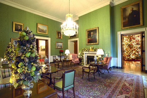 One of the finest pieces of art in the White House, the portrait of Benjamin Franklin by David Martin, is the centerpiece of the Green Room. Topiaries of gold and green fruit stand on either side of the sofa and brilliant red poinsettias and fresh green pears. White House photo by Tina Hager.