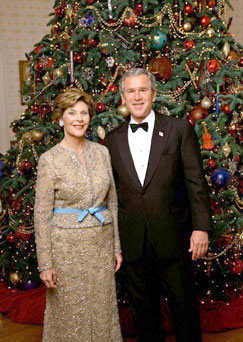 President George W. Bush and Laura Bush stand in front of the official White House Christmas Tree during the 2004 holiday season in the Blue Room of the White House. The White House celebrates the holidays with, A Season Of Merriment and Melody, and include items like 350 instrument ornaments that adorn the Blue Room tree.