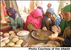 Photo of women making bread with wheat provided as part of humanitarian relief efforts. Photo courtesy of the USAID