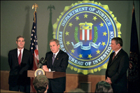 President Bush addresses the media during a tour of FBI headquarters with director Robert Mueller, left, and Attorney General John Ashcroft Sept. 25. White House photo by Paul Morse.