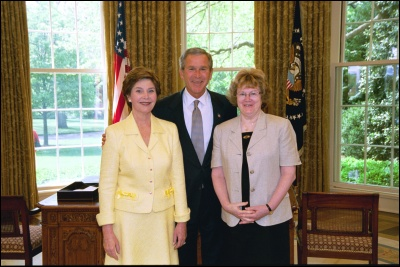 President George W. Bush and Laura Bush congratulate 2003 Maine Teacher of the Year Sharon Crossen in the Oval Office Wednesday, April 30, 2003. White House Photo by Eric Draper