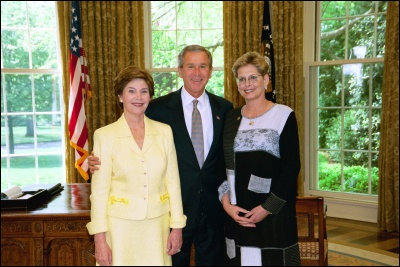 President George W. Bush and Laura Bush congratulate 2003 Maine Teacher of the Year Carol T. Hines in the Oval Office Wednesday, April 30, 2003. White House Photo by Eric Draper