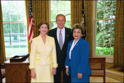 President George W. Bush and Laura Bush congratulate 2003 Maine Teacher of the Year Virginia Avila in the Oval Office Wednesday, April 30, 2003. White House Photo by Eric Draper