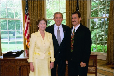 President George W. Bush and Laura Bush congratulate 2003 Maine Teacher of the Year Rich Mayorga in the Oval Office Wednesday, April 30, 2003. White House Photo by Eric Draper