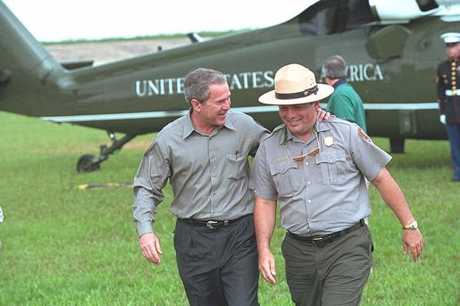 President George W. Bush talks with national park service officers at the Royal Palm Visitors Center at Everglades National Park, Fla., June 4, 2002. White House photo by Eric Draper.