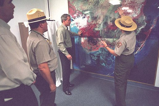 President George W. Bush looks over a topography map with national park service officer upon arriving at the Royal Palm Visitors Center at Everglades National Park, Fla., June 4, 2001. White House photo by Eric Draper.