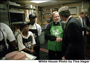 Visiting the kitchen of So Others Might Eat charity, President George W. Bush greets director Father Adams and other volunteers at the Washington D. C. site Nov. 20. White House photo by Tina Hager.