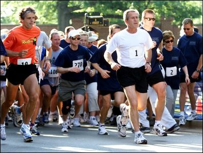 President George W. Bush starts the 3 mile run while Mrs. Bush, number 2, starts the 1.5 mile walk at Ft. McNair as part of The President's Fitness Challenge on Saturday June 21, 2002.