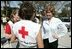 "Laura Bush speaks with American Red Cross Disaster Relief workers at the Vero Beach Community Center where disaster relief is offered to local residents Oct. 1, 2004. Vero Beach, Fla., was one of the areas hardest hit by Hurricanes Jeanne and Frances. ""See, these volunteers show the true heart of America, because we're a compassionate people, we care when a neighbor hurts, we long to help somebody when help is needed,"" said President Bush during a visit with volunteers in Stuart, Fla., Sept. 30. ""They have the gratitude of all they've served, and they have the admiration for our whole country."""