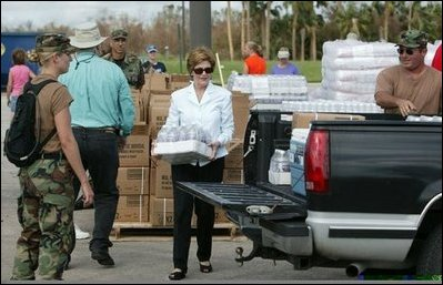 Laura Bush works with volunteers and The Army National Guard at the Indian River County Distribution Center passing out water, ice and Meals Ready To Eat, MRE, to residents in Vero Beach, Fla., Oct. 1, 2004.