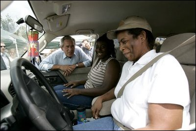 Helping pass out water, President Bush visits with residents affected by Hurricane Frances at an emergency relief center in Ft. Pierce, Fla., Sept. 8, 2004.