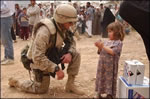 U.S. Marine Corps Major Chris Hughes shares some time with an Iraqi girl during an effort to distribute food and water to Iraqi citizens in need.