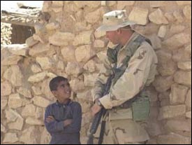 A soldier from the 422nd Civil Affairs Battalion speaks with a boy, while bags of rice and wheat are delivered to a village near the city of Najaf in central Iraq on April 04, 2003, during Operation Iraqi Freedom. (DoD photo by Staff Sgt. Kevin P. Bell, U.S. Army.)