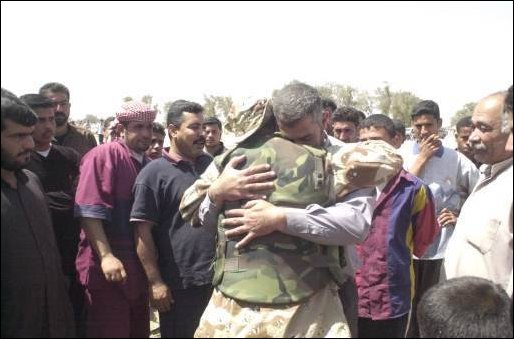 A member of the Free Iraqi Forces (FIF) has a reunion with famly members at Umm Qasr, Iraq,.
