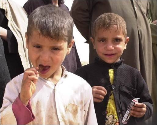 The children's of a local Iraqi family in the community enjoy a tootsie roll.