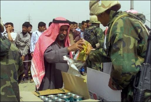 Marines from TF Tarawa hand out needed food and supplies to Iraqi citizens near An Nasariyah, Iraq.