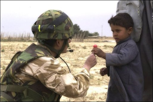 An RAF Regiment gunner shares sweets with an Iraqi child.