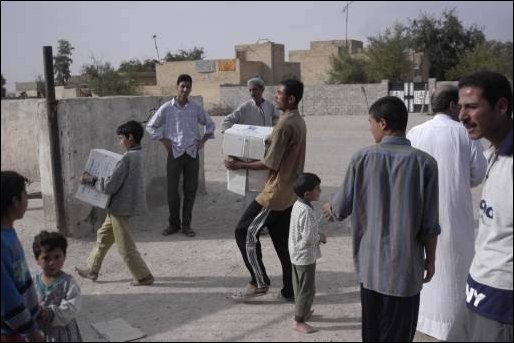 Local Basra residents help Special Operation Civil Affairs Soldiers unload school supplies in Iraq, April 4, 2003. The school supplies, stockpiled with other humanitarian aid materials by the Saddam Hussein regime are now finding their way to their originally intended destinations. (U.S. Army photo by Spc. Thomas Mund).
