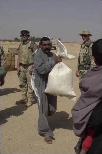 A man carries a bag of rice provided by an international relief agency and delivered by soldiers from the 422nd Civil Affairs Battalion in a village near the city of Najaf in central Iraq on April 04, 2003. (DoD photo by Staff Sgt. Kevin P. Bell, U.S. Army.)