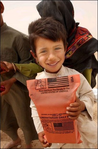 An Iraqi boy holds a humanitarian food ration given to him by U.S. Army soldiers during an effort to distribute food and water to Iraqi citizens in need.