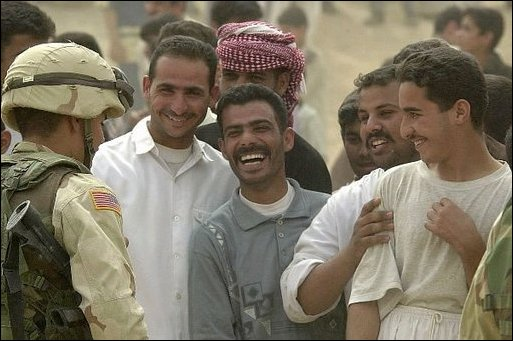 Iraqis share a laugh with a U.S. Army Specialist Michael Toro during an effort to distribute food and water to Iraqi citizens in need.