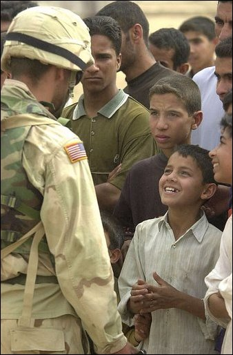 An Iraqi boy smiles as he talks with a U.S. Army soldier during an effort to distribute food and water to Iraqi citizens in need.