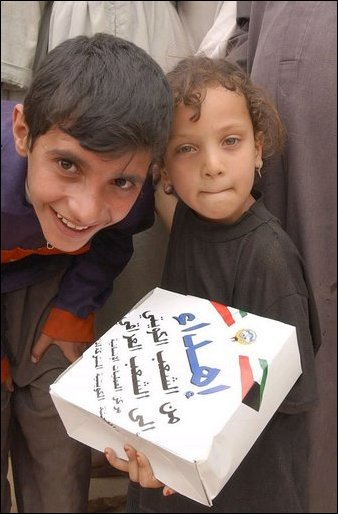 Iraqi children show humanitarian food rations distributed by citizens of Kuwait and U.S. Army soldiers during an effort to distribute food and water to Iraqi citizens in need.