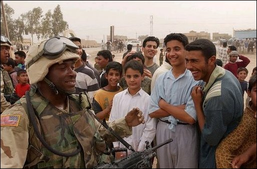 Iraqis share a laugh with a U.S. Army soldier during an effort to distribute food and water to Iraqi citizens in need.
