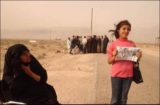 A local Iraqi girl shows her enthusiasm for the US being in Iraq with a homemade sign. Her family waits to find if one of their relatives is among the thousands of Enemy Prisoners of War (EPW) in a nearby EPW camp. (US Navy photo by PH1(SW) Aaron Ansarov)