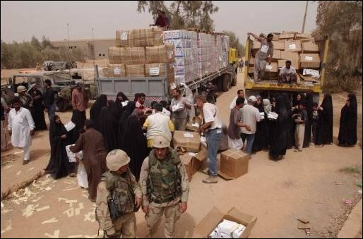 Iraqi volunteers from the city of An Najaf work hand in hand with Kuwaiti volunteers to help to unload water for needy residents during a food and water distribution. The coordinated effort between volunteers citizens from Kuwait and the U.S. Military is helping to provide food and medicine for needy Iraqi people in support of Operation Iraqi Freedom.
