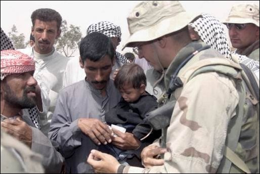 Navy Doctor Lieutenant Charles Presenza from MWSS-271, gives medical advice to Iraqis on April 8, 2003. Corpsman from MWSS-271 visited a farm village near Three Rivers as part of humanitarian aid in support of Operation Iraqi Freedom.