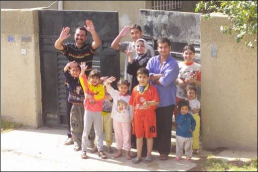 An Iraqi family waves to the Marines of Charlie Company 1st Tank Battalion along Highway 6, April 14, 2003.