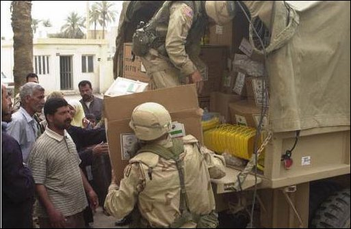 A local Basra schoolboy helps Special Operation Civil Affairs Soldiers unload school supplies in Iraq, April 4, 2003. The school supplies, stockpiled with other humanitarian aid materials by the Saddam Hussein regime are now finding their way to their originally intended destinations. (U.S. Army photo by Spc. Thomas Mund)