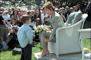 "Laura Bush takes a moment for a little reader during one of the many story book hours at the annual White House Easter Egg Roll on the South Lawn of the White House April 1, 2002. Several cabinet secretaries, such as Rod Paige and Norman Mineta, gave readings. Marc Brown, who wrote the children's book ""Arthur Meets the President"" was one of several authors who read their stories as well."
